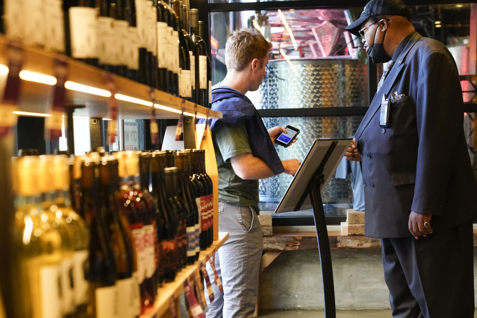 Security personnel ask customers for proof of vaccination as they enter City Winery Thursday, June 24, 2021, in New York. Customers wanting to wine, dine and unwind to live music at the City Winery's flagship restaurant in New York must show proof of a COVID-19 vaccination to get in. But that's not required at most other dining establishments in the city. And it's not necessary at other City Winery sites around the U.S. (AP Photo/Frank Franklin II)