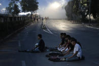 Muslim students perform an evening prayer as smoke from tear gas billows in the background during a clash with riot police in Jakarta, Indonesia, Monday, Sept. 30, 2019. Thousands of Indonesian students resumed protests on Monday against a new law they say has crippled the country's anti-corruption agency, with some clashing with police. (AP Photo/Dita Alangkara)