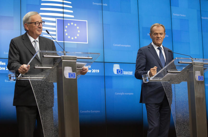 European Commission President Jean-Claude Juncker, left, and European Council President Donald Tusk participate in a media conference at an EU summit in Brussels, Friday, Oct. 18, 2019. After agreeing on terms for a new Brexit deal, European Union leaders are meeting again to discuss other thorny issues including the bloc's budget and climate change. (AP Photo/Virginia Mayo)