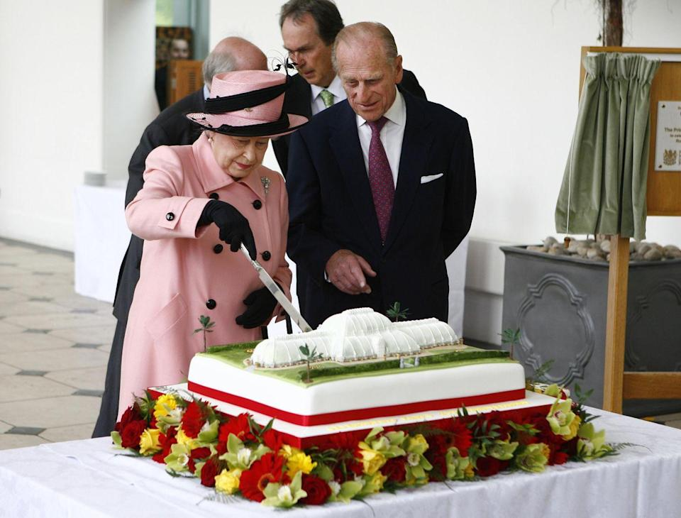 <p>Prince Philip looked on while the Queen sliced a molded cake, celebrating the Royal Botanic Gardens at Kew's 250th anniversary. </p>
