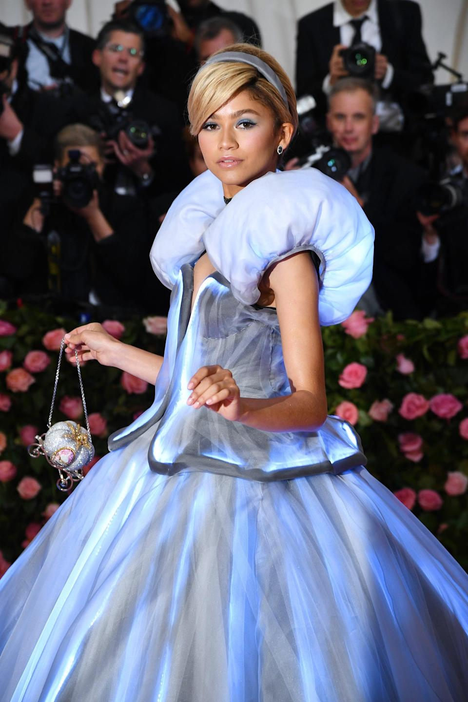 """<p><a class=""""link rapid-noclick-resp"""" href=""""https://www.popsugar.co.uk/Zendaya"""" rel=""""nofollow noopener"""" target=""""_blank"""" data-ylk=""""slk:Zendaya"""">Zendaya</a> went for a more overt homage when she <a href=""""https://www.popsugar.com/fashion/Zendaya-Cinderella-Dress-2019-Met-Gala-46119928"""" class=""""link rapid-noclick-resp"""" rel=""""nofollow noopener"""" target=""""_blank"""" data-ylk=""""slk:dressed like Cinderella"""">dressed like Cinderella</a> to attend the 2019 Met Gala. The baby blue Tommy Hilfiger gown lit up as soon as she hit the <a href=""""https://www.popsugar.com/fashion/Met-Gala-Red-Carpet-Dresses-2019-46110280"""" class=""""link rapid-noclick-resp"""" rel=""""nofollow noopener"""" target=""""_blank"""" data-ylk=""""slk:camp-themed red carpet"""">camp-themed red carpet</a>, and a velvet headband, choker necklace, and carriage-shaped purse helped complete the princess look. Law, meanwhile, attended the event as the Fairy Godmother in a fitting move.</p>"""