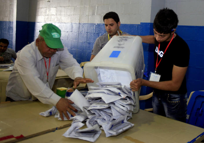 Iraqi electoral workers empty a ballot box at a counting center in Baghdad, Iraq, Sunday, April 21, 2013. Iraqis have begun counting votes from the first provincial elections since the last U.S. troops withdrew in December 2011. (AP Photo/ Karim Kadim)