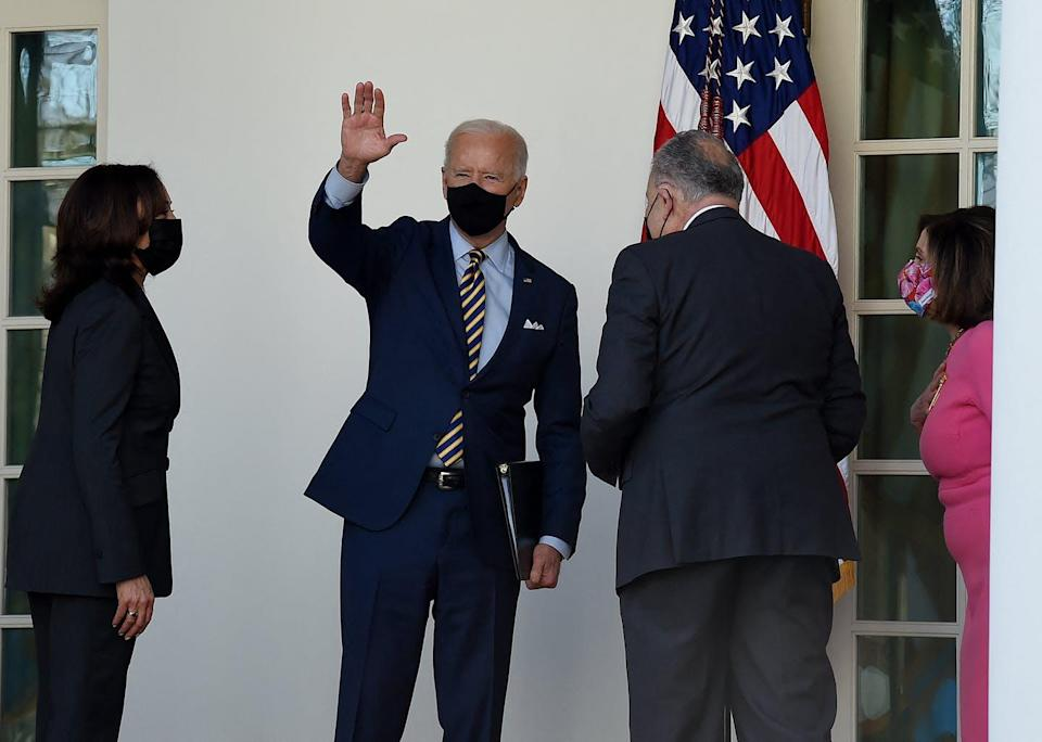 President Biden, waving while standing with Vice President Harris, Sen. Schumer and Rep. Pelosi