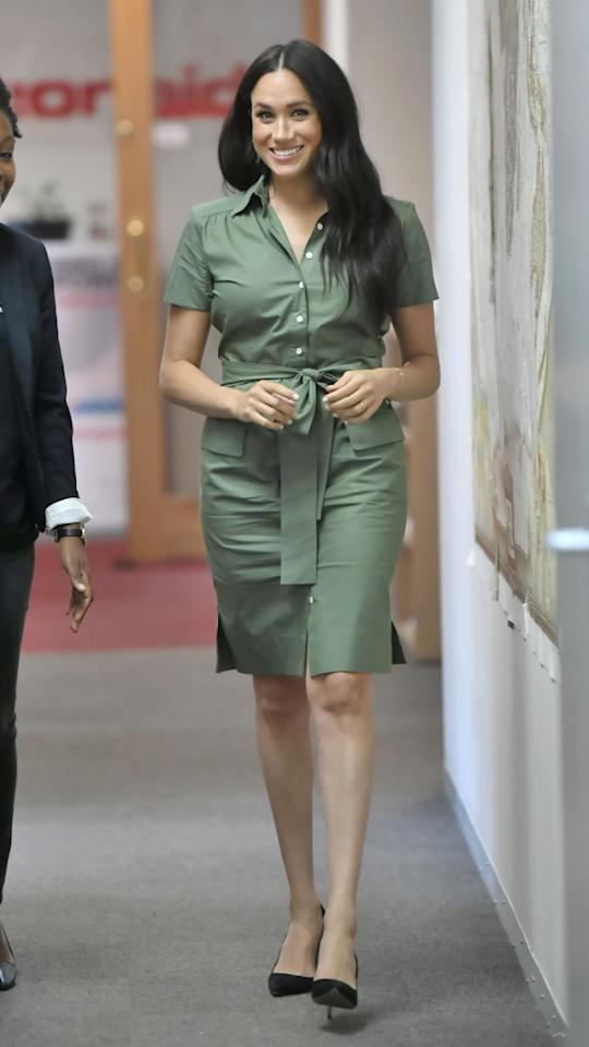"Meghan opted for a now sold-out <a href=""https://room502.com/collections/serie-1-limited-edition/products/stephanie?variant=29489070145618"">£371 ethically-sourced khaki shirt dress</a> by American-brand Room 502 for her second engagement of the day. She styled the look with a pair of black court shoes. <em>[Photo: Getty]</em>"