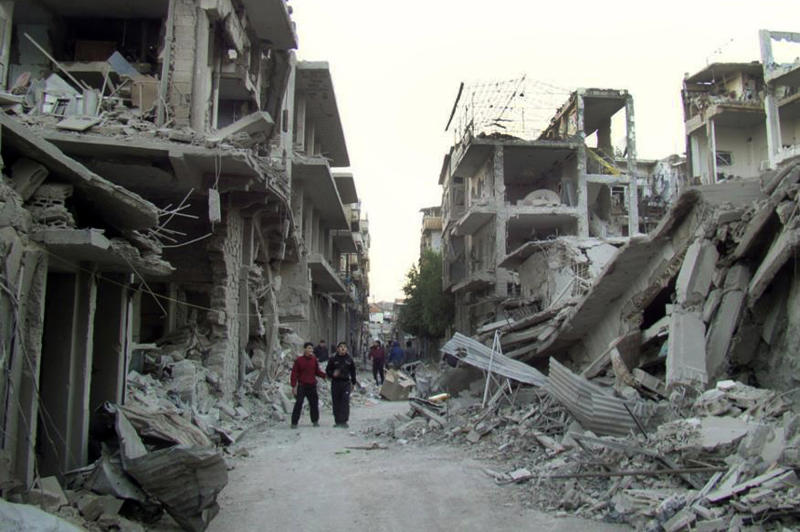 FILE - In this file photo released on Thursday, Nov. 29, 2012 by the anti-government activist group Homs City Union of The Syrian Revolution, which has been authenticated based on its contents and other AP reporting, Syrian citizens walk in a destroyed street that was attacked by Syrian warplanes, at Abu al–Hol street in Homs province, Syria. Exhausted and worn out from a year-long siege, hundreds of Syrian rebels on Wednesday, May 7, 2014, left their last remaining bastions in the heart of Homs under a ceasefire deal with government forces. (AP Photo/Homs City Union of The Syrian Revolution, File)