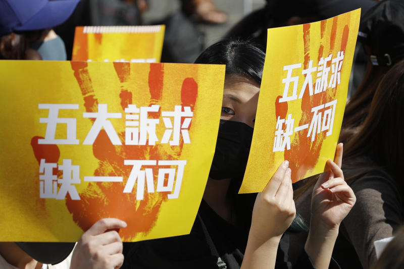 """Pro-democracy supporters hold up cards which read """"Five Demands, Not one less"""" during a rally by the advertising industry in Hong Kong Monday, Dec. 2, 2019. Thousands of people took to Hong Kong's streets Sunday in a new wave of pro-democracy protests, but police fired tear gas after some demonstrators hurled bricks and smoke bombs, breaking a rare pause in violence that has persisted during the six-month-long movement. (AP Photo/Vincent Thian)"""
