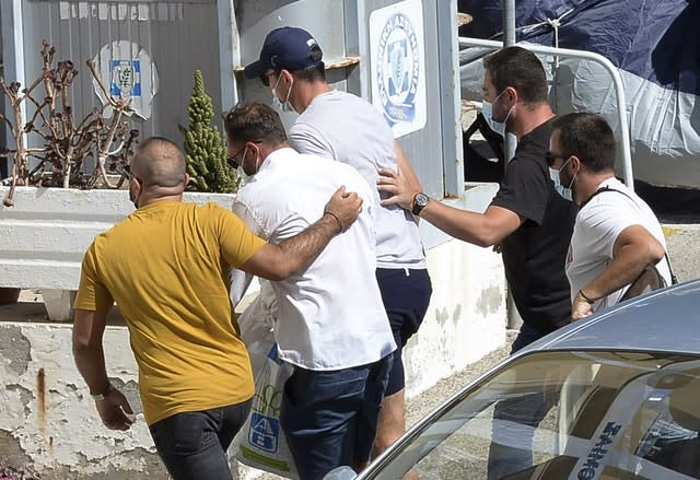 Harry Maguire, with the blue cap, escorted by plain clothed officers at the police station on Syros