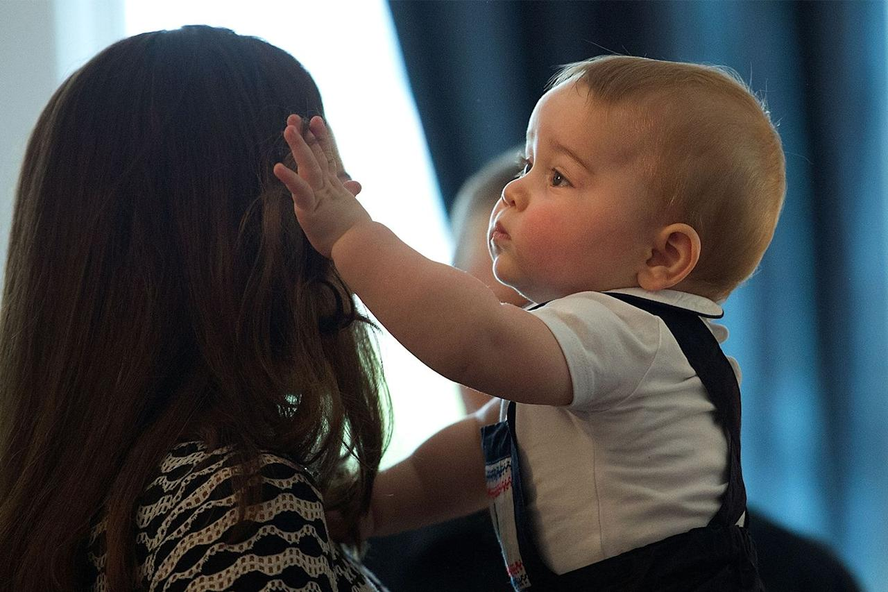 """<p>At nine months old, George played with the <a href=""""https://www.marieclaire.com/beauty/a15926802/kate-middleton-elnett-hairspray/"""" target=""""_blank"""">Duchess of Cambridge's hair</a> oh-so-lovingly during their official visit to New Zealand. The trip marked Kate and William's first journey overseas with their baby boy.</p>"""