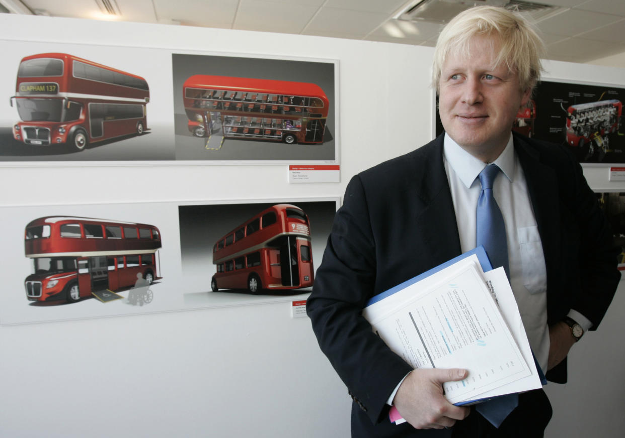London's Mayor Boris Johnson stands next to some of the winning designs that will lead to the next generation of the London's famous red Routemaster bus, at an award ceremony in London Friday, Dec. 19, 2008. It is  hoped that the new bus which will incorporate the best of the winning designs will be on London streets in late 2011.(AP Photo/Alastair Grant)