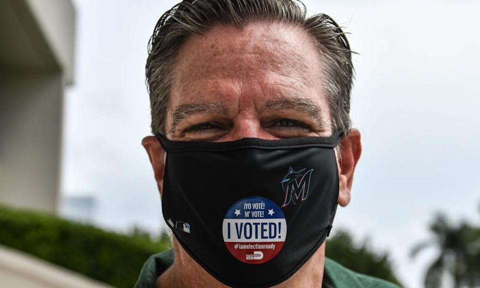 """A man displays his """"I Voted"""" sticker on his face mask in Miami Beach, Florida."""