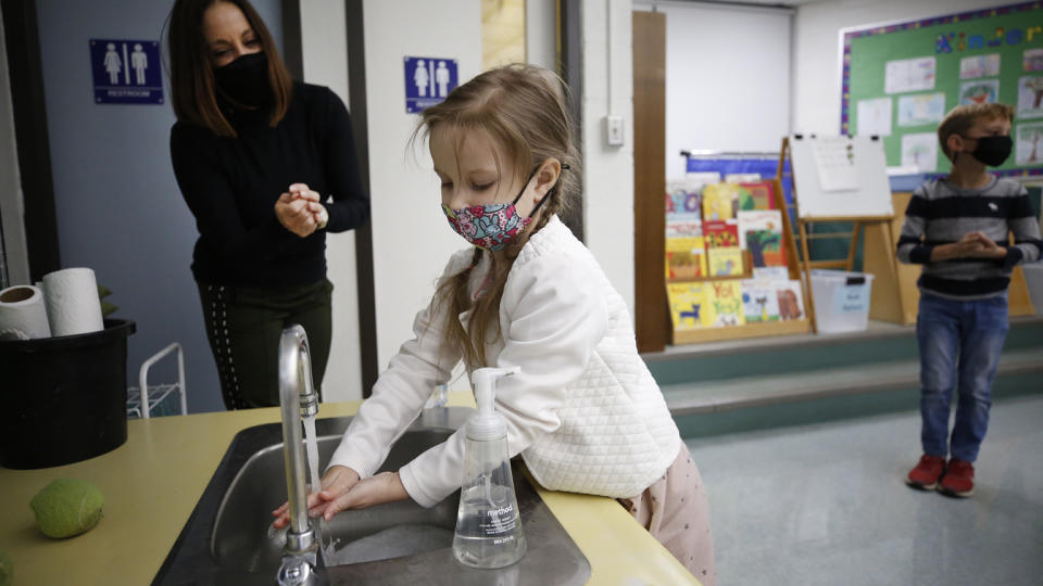 Kindergarten teacher assistant Susan Silic assist student with proper hand washing in the classroom at Lupine Hill Elementary School in Calabasas as one of the first elementary schools to open up under in L.A. County Monday morning. (Al Seib/Los Angeles Times via Getty Images)
