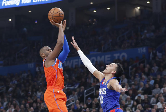 Oklahoma City Thunder guard Chris Paul, left, shoots as Los Angeles Clippers guard Landry Shamet (20) defends during the second quarter of an NBA basketball game Sunday, Dec. 22, 2019, in Oklahoma City. (AP Photo/Alonzo Adams)