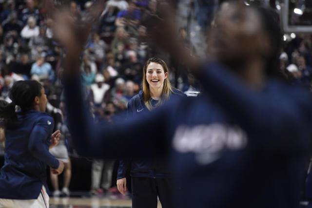 Connecticut's Katie Lou Samuelson watches her teammates warm up before an NCAA college basketball game in the American Athletic Conference tournament quarterfinals against East Carolina, Saturday, March 9, 2019, at Mohegan Sun Arena in Uncasville, Conn. Samuelson is sitting out the tournament with an injury. (AP Photo/Jessica Hill)