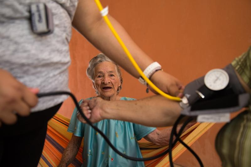 Abdona Villonueva suffers from dementia and Alzheimer's but still happily spends her time swinging on her hammock in her home in Aguada. She is cared for by her daughter Carmen who is having her blood pressure checked while Abdona watches. (Alex Kormann)