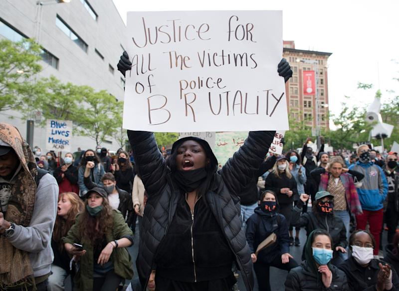 A anti-police brutality protester hold a sign during a demonstration calling for justice in the death of George Floyd and victims of police brutality in Montreal on May 31, 2020. (Photo: Graham Hughes/CP)