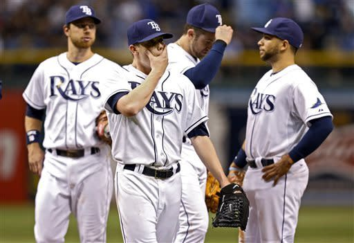 Tampa Bay Rays starting pitcher Jeremy Hellickson, second from left, reacts in front of teammates, from left, Ben Zobrist, Evan Longoria and James Loney after being removed from the game following a grand slam home run by San Diego Padres' Jesus Guzman during the seventh inning of an interleague baseball game Saturday, May 11, 2013, in St. Petersburg, Fla. (AP Photo/Mike Carlson)