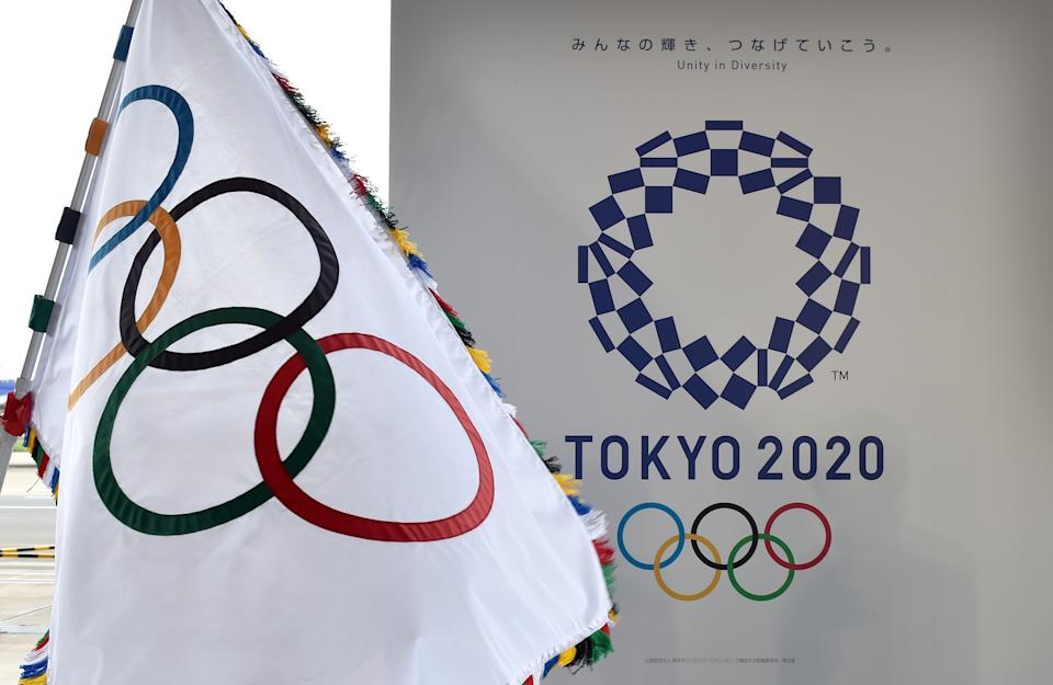 The Olympic flag (L) and the logo of the Tokyo 2020 are displayed during the official flag arrival ceremony at the Tokyo's Haneda airport on August 24, 2016. - The Olympic flag arrived in Tokyo on August 24, as Japan's capital gears up to host the 2020 Games, with officials promising smooth sailing after Rio's sometimes shaky 2016 instalment. (Photo by KAZUHIRO NOGI / AFP)        (Photo credit should read KAZUHIRO NOGI/AFP via Getty Images)