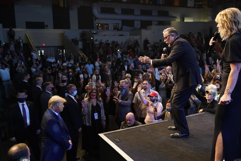 President Donald Trump, lower left, attends church at International Church of Las Vegas, as Pastor Pasqual Urrabazo, second from the right, gestures on stage, Sunday, Oct. 18, 2020, in Las Vegas, Nev. (AP Photo/Alex Brandon)