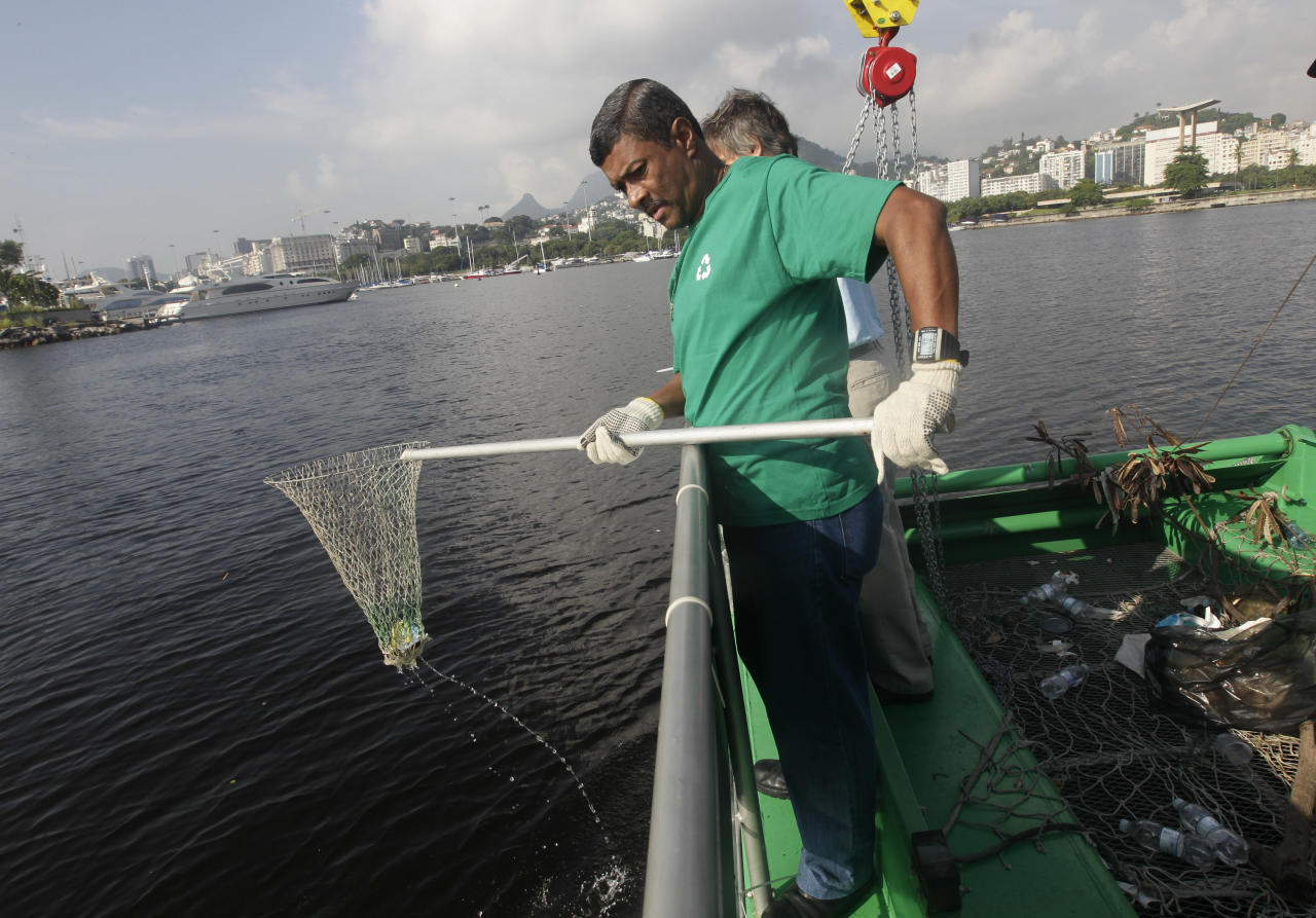 "A worker fishes out trash from a garbage-collecting barge at the Guanabara bay, in Rio de Janeiro, Brazil, Monday, Jan. 6, 2014. The green barge plies the polluted waters of Rio de Janeiro's Guanabara Bay alongside wooden fishing boats but its catch consists not of grouper or swordfish but rather plastic bags, empty soda bottles and a discarded toilet seat. The barge is one of three so-called ""eco-boats,"" floating garbage vessels that are a key part of authorities' pledge to clean up Rio's devastated Guanabara Bay before the city – and the waterway itself – plays host to the 2016 Olympic games. (AP Photo/Silvia Izquierdo)"