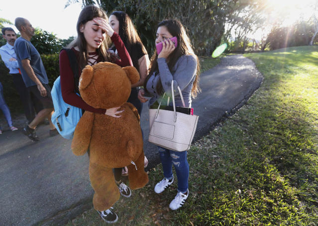 <p>Students wait to be picked up after a shooting at Marjory Stoneman Douglas High School in Parkland, Fla., Feb. 14, 2018. (Photo: Wilfredo Lee/AP) </p>