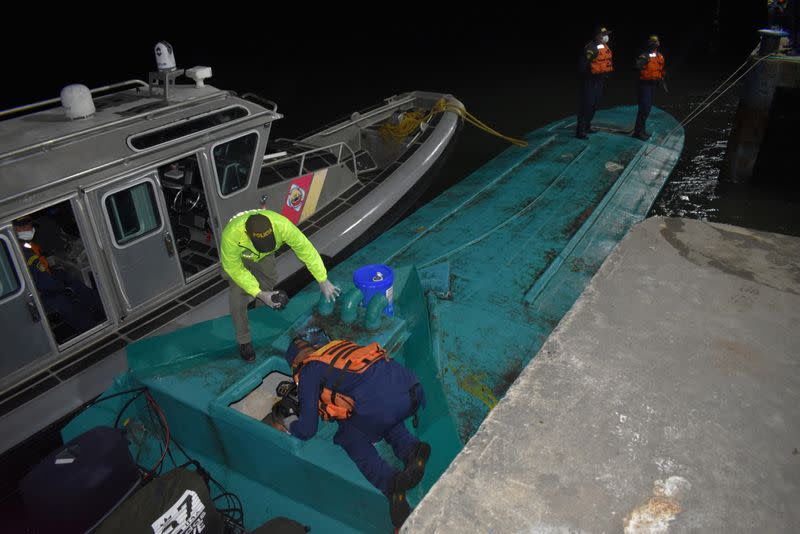FILE PHOTO: A police officer and navy officers wearing face masks due to the ongoing coronavirus disease (COVID-19) outbreak, inspect a semi-submersible sea vessel loaded with more than a ton of cocaine hydrochloride during a seizure operation in Tumaco