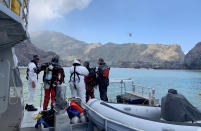 Police divers prepare to search the waters near White Island off the coast of Whakatane, New Zealand, Saturday Dec. 14, 2019. A team of nine from the Police National Dive Squad resumed their search at early Saturday for a body seen in the water following Monday's volcanic eruption. (New Zealand Police via AP)