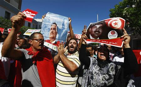 Protesters hold up and a picture of slain opposition leader Brahmi during anti-government demonstration rallying for the dissolution of the Islamist-led government in Sfax
