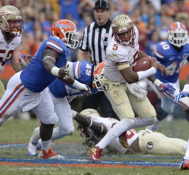 Florida State quarterback Jameis Winston (5) tries to get away from Florida State tight end Giorgio Newberry (4) During the first half of an NCAA college football game Saturday, Nov. 30, 2013 in Gainesville, Fla. Florida State defeated Florida 37-7. (AP Photo/Phil Sandlin)