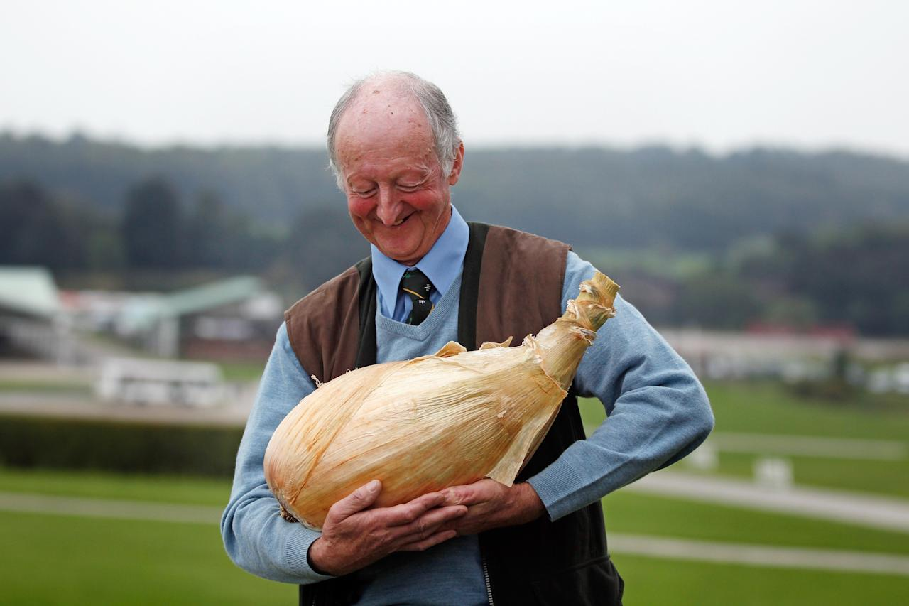 HARROGATE, ENGLAND - SEPTEMBER 16:  Gardener Peter Glazebrook cradles his world record breaking onion as he poses for photographers at The Harrogate Flower Show on September 16, 2011 in Harrogate, England. Peter Glazebrook from Newark, Nottinghamshire claimed a Guinness World Record with his giant onion weighing 8.150kg.  (Photo by Christopher Furlong/Getty Images)