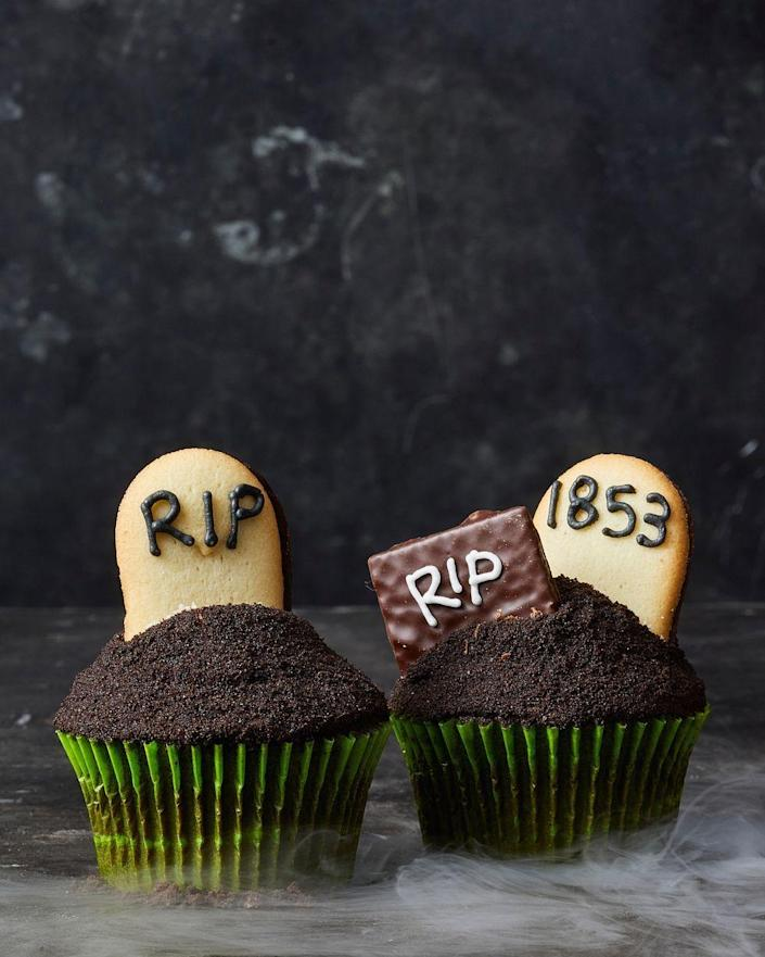 """<p>Set a spooky scene on top of deep dark chocolate cupcakes.</p><p>Get the recipe from <a href=""""https://www.goodhousekeeping.com/food-recipes/party-ideas/a28591112/graveyard-cupcakes-recipe/"""" rel=""""nofollow noopener"""" target=""""_blank"""" data-ylk=""""slk:Good Housekeeping"""" class=""""link rapid-noclick-resp"""">Good Housekeeping</a>.</p>"""