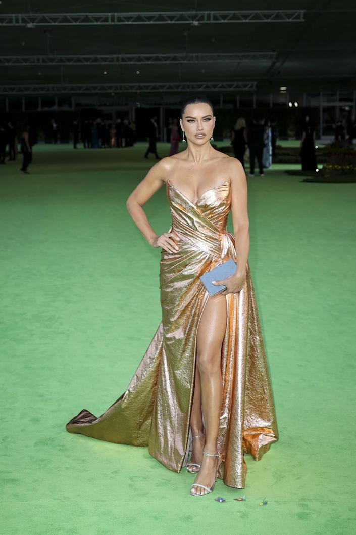 A woman in a gold dress posing on a green carpet