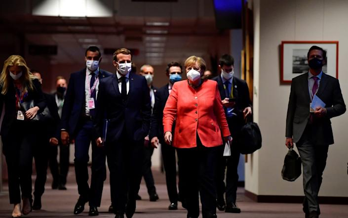 German Chancellor Angela Merkel and French President Emmanuel Macron arrive for a joint press conference at the end of the European summit - Reuters