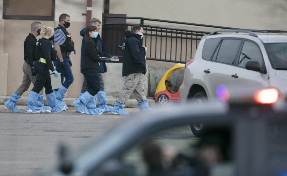Police wearing forensic shoe covers at the scene of the Boulder shooting.