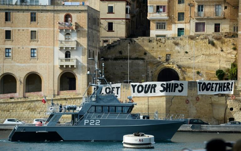 "Protesters display a banner reading ""EU Get Your Ships Together"" in Malta, where four interior ministers met"