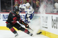 Carolina Hurricanes defenseman Brady Skjei (76) and Tampa Bay Lightning center Anthony Cirelli (71) chase the puck during the first period in Game 1 of an NHL hockey Stanley Cup second-round playoff series in Raleigh, N.C., Sunday, May 30, 2021. (AP Photo/Gerry Broome)