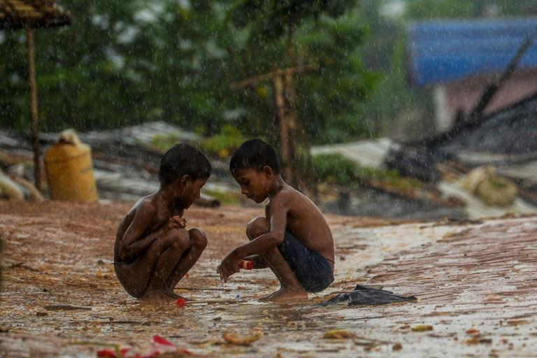 Rohingya refugee children play during rainfall at the Kutupalong refugee camp in Bangladesh, where a Rohingya leader said the ban on mobile phone services will greatly affect the refugees' lives (AFP Photo/MUNIR UZ ZAMAN)