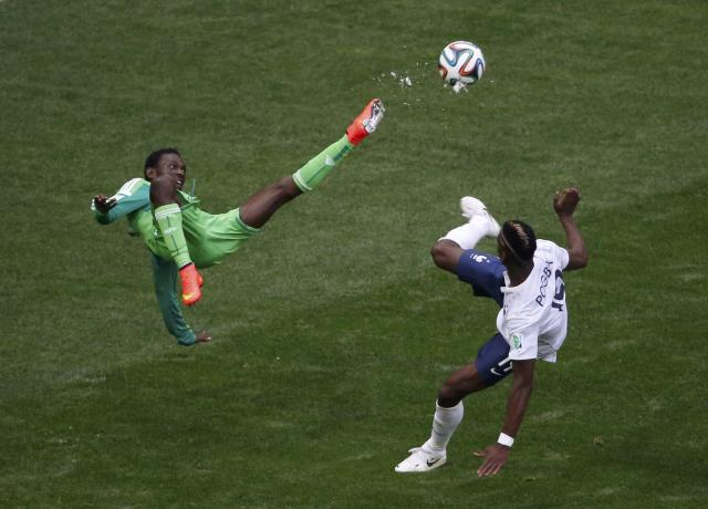 Nigeria's Juwon Oshaniwa (L) fights for the ball with France's Paul Pogba during their 2014 World Cup round of 16 game at the Brasilia national stadium in Brasilia June 30, 2014. REUTERS/David Gray (BRAZIL - Tags: SOCCER SPORT WORLD CUP TPX IMAGES OF THE DAY)