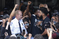 Richmond Police Chief William Smith, left, is confronted by a protester as he attempts to address a large crowd in front of City Hall, Tuesday June 2, 2020, in Richmond, Va. Richmond Mayor Levar Stoney apologized after police, the night before, lobbed tear gas at a group of peaceful demonstrators during a protest over the death of George Floyd, who died after being restrained by Minneapolis police officers on May 25. (AP Photo/Steve Helber)