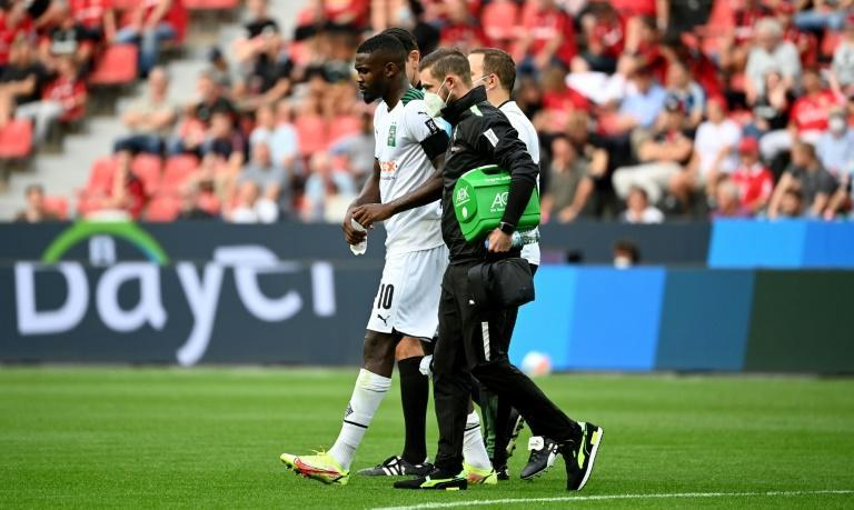 Moenchengladbach French forward Marcus Thuram (C) had to be helped off at Leverkusen with a knee injury