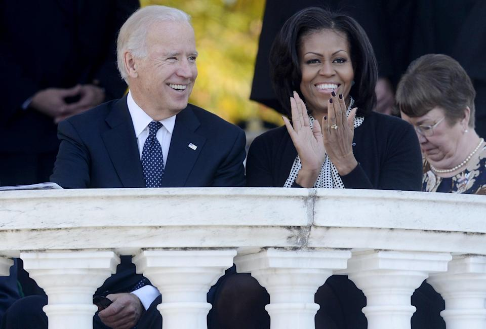 ARLINGTON, VA - NOVEMBER 11: US Vice President Joe Biden (L) and First Lady Michelle Obama (R) attend a ceremony on Veteran's Day at the Tomb of the Unknown Soldier in Arlington National Cemetery on November 11, 2012 in Arlington, Virginia. (Photo by Michael Reynolds-Pool/Getty Images)