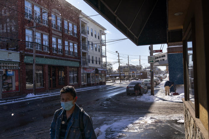 A man shovels snow along a busy commercial street in Central Falls, R.I., Saturday Feb. 20, 2021. Residents in the hard-hit community of Central Falls live in dense rows of triple-decker homes and apartment complexes and are the workforce for the states capital of Providence to the south. (AP Photo/David Goldman)