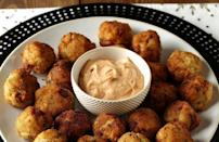 """<p>Traditionally a food eaten for good luck in the new year, sauerkraut balls are an underrated fried food appetizer. The salty combo of ham, sauerkraut, pickle and potato will surely become a family favorite.</p> <p><a href=""""https://www.thedailymeal.com/best-recipes/crispy-sauerkraut-ham-fritters?referrer=yahoo&category=beauty_food&include_utm=1&utm_medium=referral&utm_source=yahoo&utm_campaign=feed"""" rel=""""nofollow noopener"""" target=""""_blank"""" data-ylk=""""slk:For the Crispy Sauerkraut-Ham Fritters recipe, click here."""" class=""""link rapid-noclick-resp"""">For the Crispy Sauerkraut-Ham Fritters recipe, click here.</a></p>"""