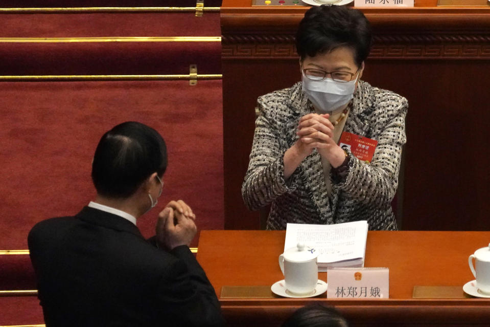 Hong Kong Chief Executive Carrie Lam, right, exchanges greetings with a fellow delegate before the opening session of China's National People's Congress (NPC) at the Great Hall of the People in Beijing, Friday, March 5, 2021. (AP Photo/Andy Wong)
