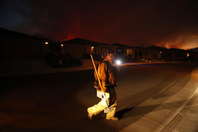<p>A firefighter looks for flammable items in an evacuated residential area as wildfires continue to burn Saturday, Oct. 14, 2017, in Santa Rosa, Calif. (Photo: Jae C. Hong/AP) </p>