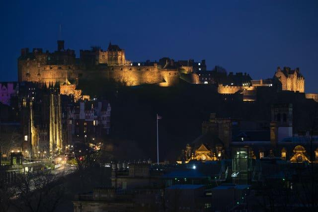 Edinburgh Castle is illuminated yellow during the National Day of Reflection