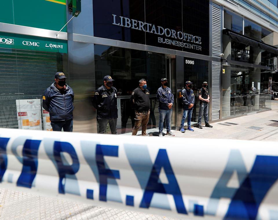 <p>Police stand guard outside the Buenos Aires office of Dr Leopoldo Luque</p> (Reuters)