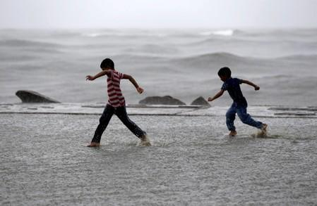 Children play in a puddle of water as it rains at a sea front in Kochi
