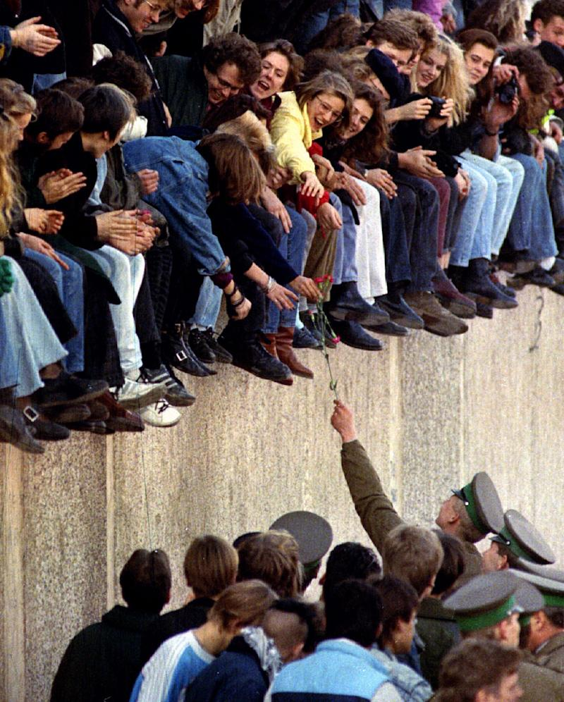An East Berlin border guard hands a flower back to West Berlin citizens who are sitting atop the Berlin Wall in front of the Brandenburg Gate. Other West Berlin citizens mingle with border guards on the East Berlin side on Nov. 9, 1989. (Photo: Reuters)