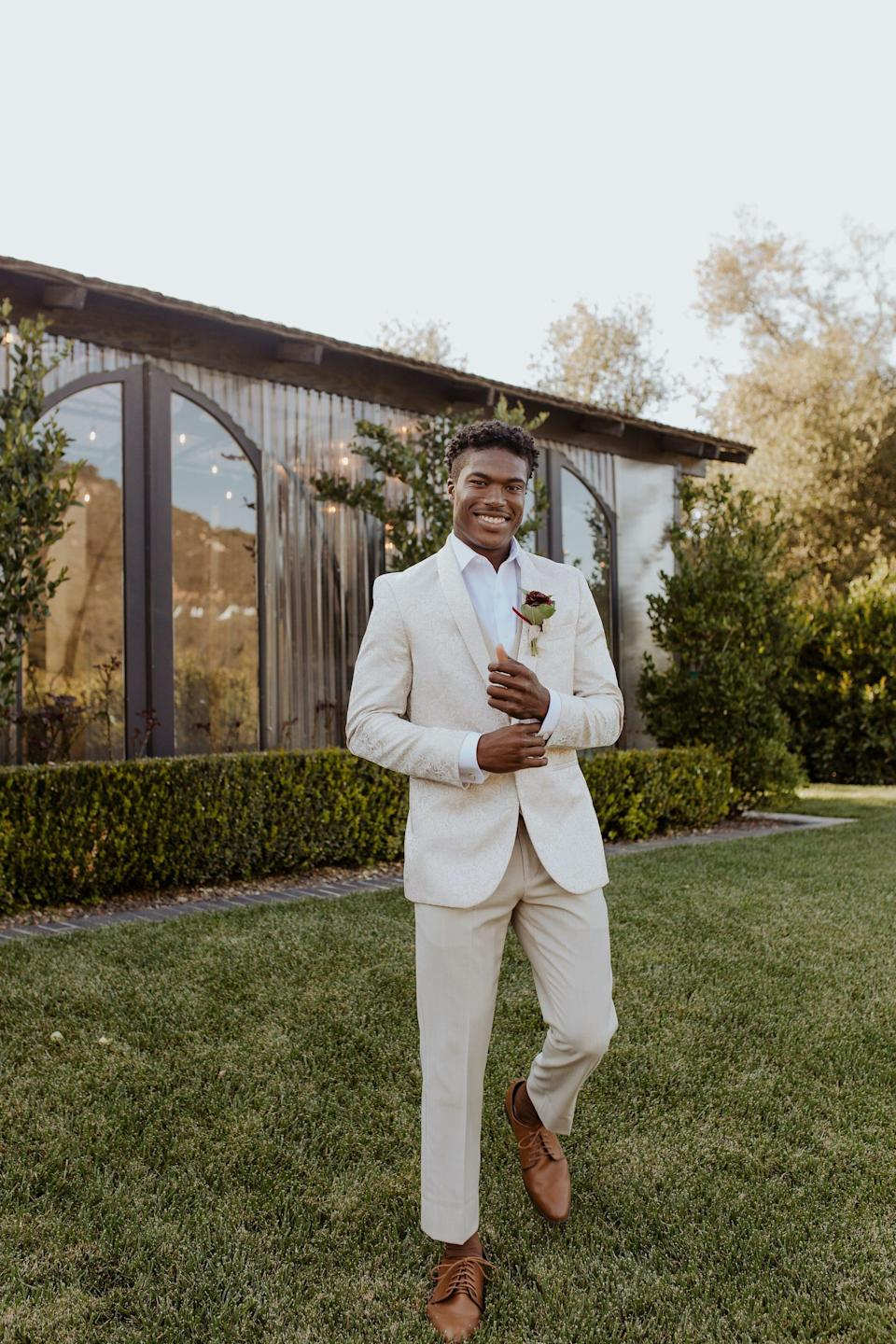 A groom stands in a field in front of a building in a cream suit.