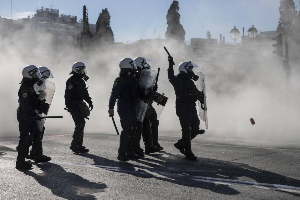 Riot police stand among smoke outside the Greek parliament during brief clashes as university students demonstrate against education reforms in Athens, Thursday, Feb. 4, 2021. Thousands of protesters in Greece have held demonstrations in the Greek capital and the second largest city of Thessaloniki against plans by the government to police university campuses. (AP Photo/Petros Giannakouris)
